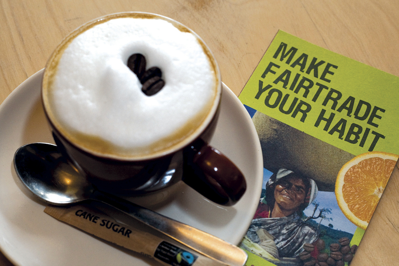 PHOTO: A cup of Fairtrade coffee on a saucer with a sachet of Fairtrade brown cane sugar
